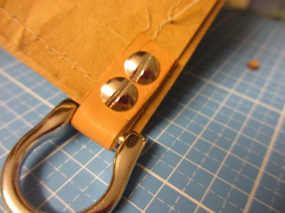 Einen Lederstreifen um den oberen Rand der Tasche legen und zur Öse formen