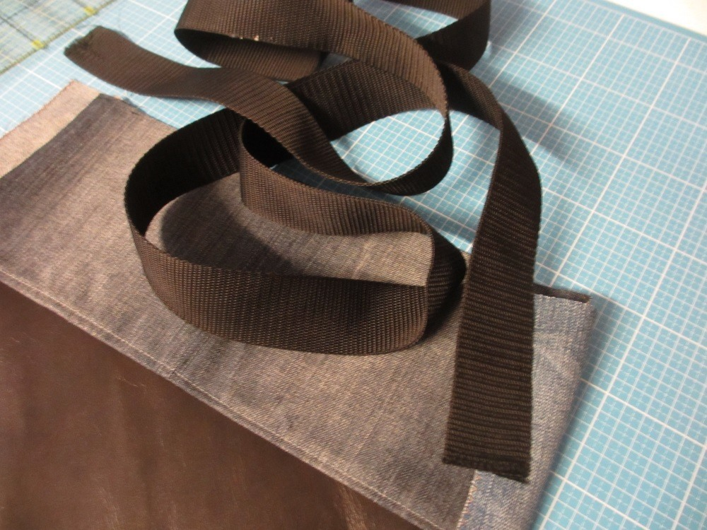 Gurtband wird an einer Seite der Tasche fest angenäht.