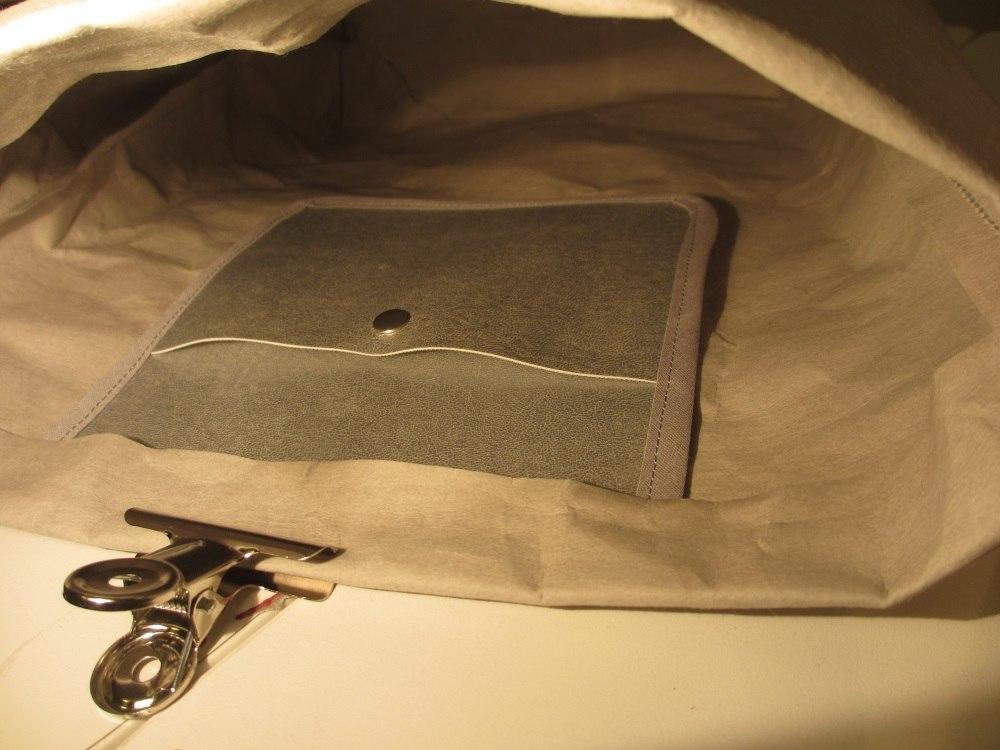 Die Innentasche mittig unter den Taschenrand schieben.