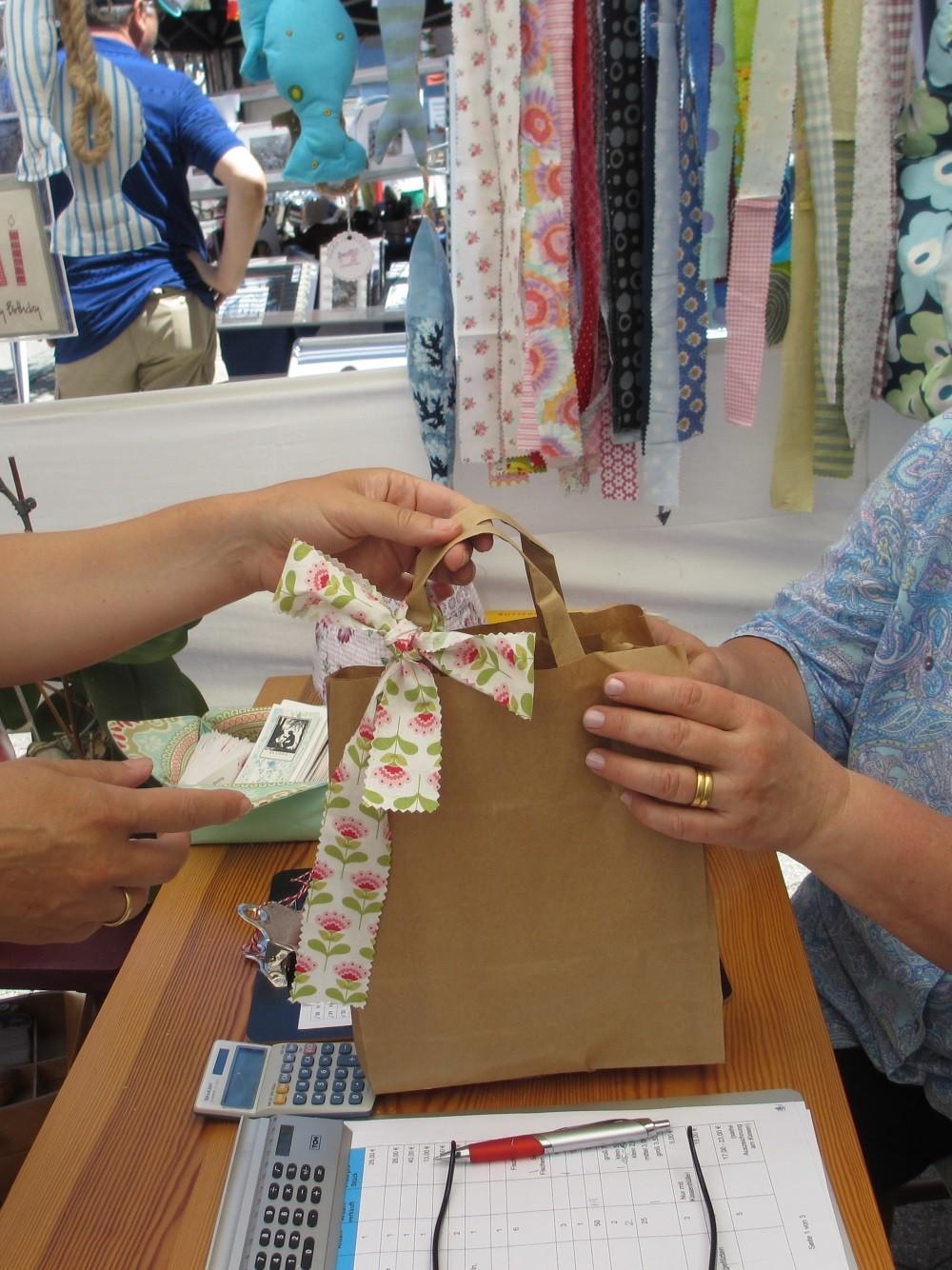 Im Hintergrund flattern die vorbereiteten Stoffbänder für die Verkaufstüte
