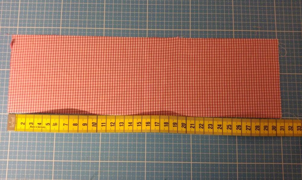 Die Länge des Trägerbandes zuzüglich der später notwendigen Nahtzugabe zuschneiden