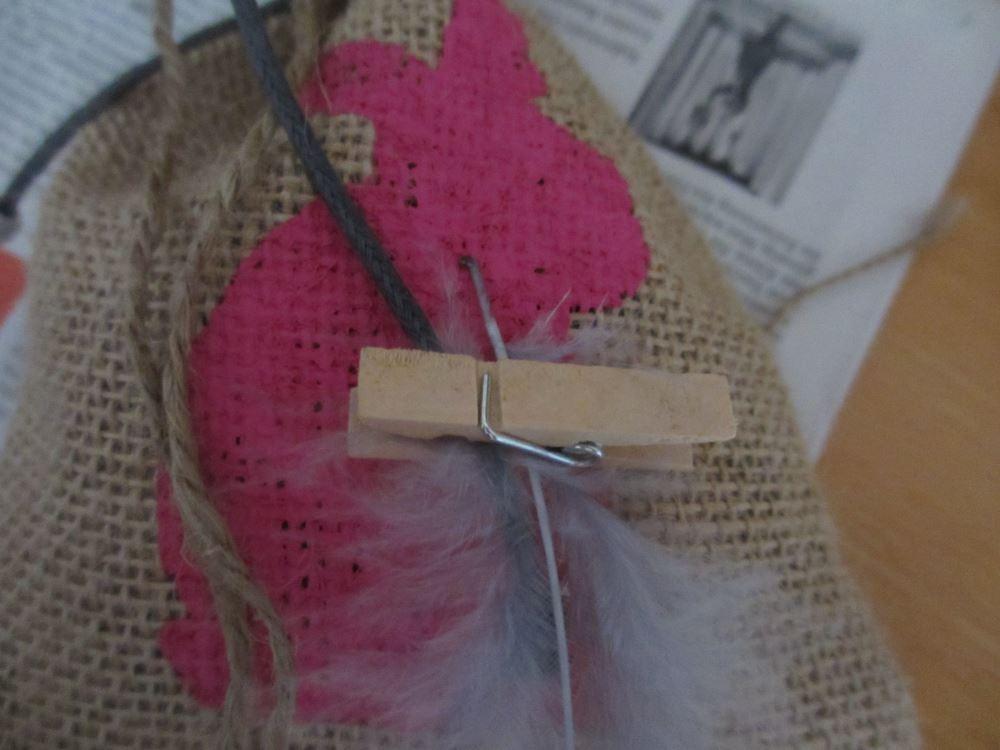 Verzierung des Säckchens mit Feder, Klammer und Schnur