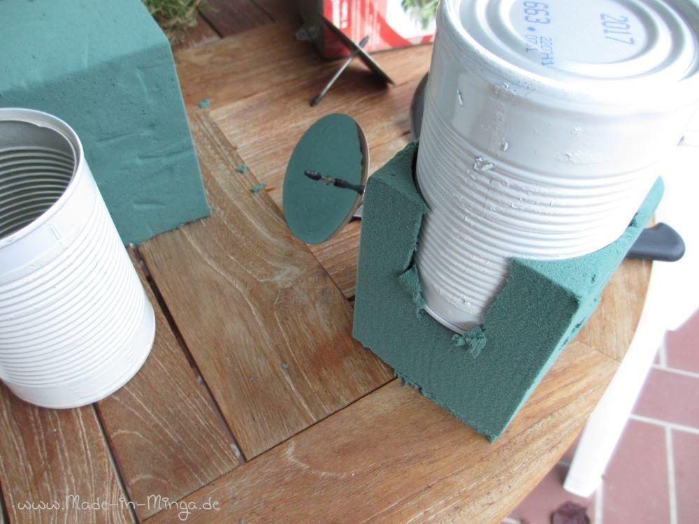 Steckschaum als Quader ungefähr auf die Größe der Dose zurechtschneiden. Die Dose von oben reindrücken und schwupps ist sie mit passendem Steckschaum gefüllt.