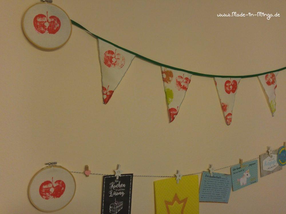 Wimpelkette und Apfel im Stickrahmen zusammen an der Wand dekorieren