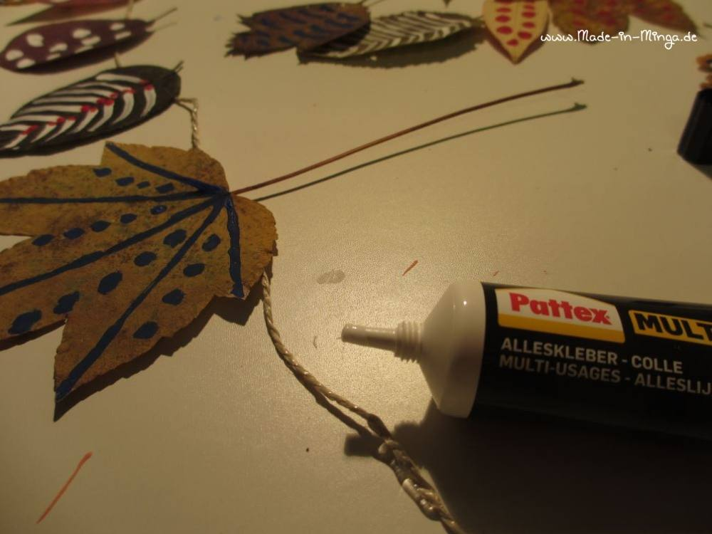 Getrocknete Blätter mit Klebstoff an der Schnur festkleben