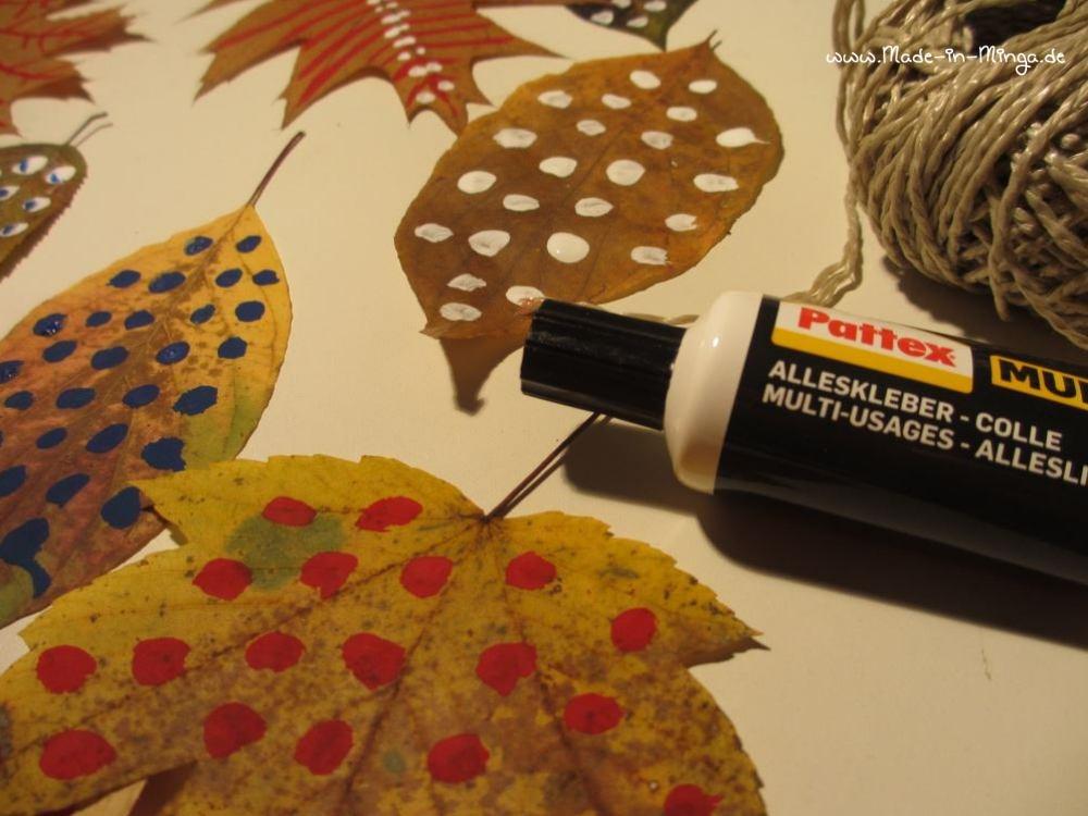 Getrocknete Blätter an einer Schnur festkleben - Herbstdeko basteln