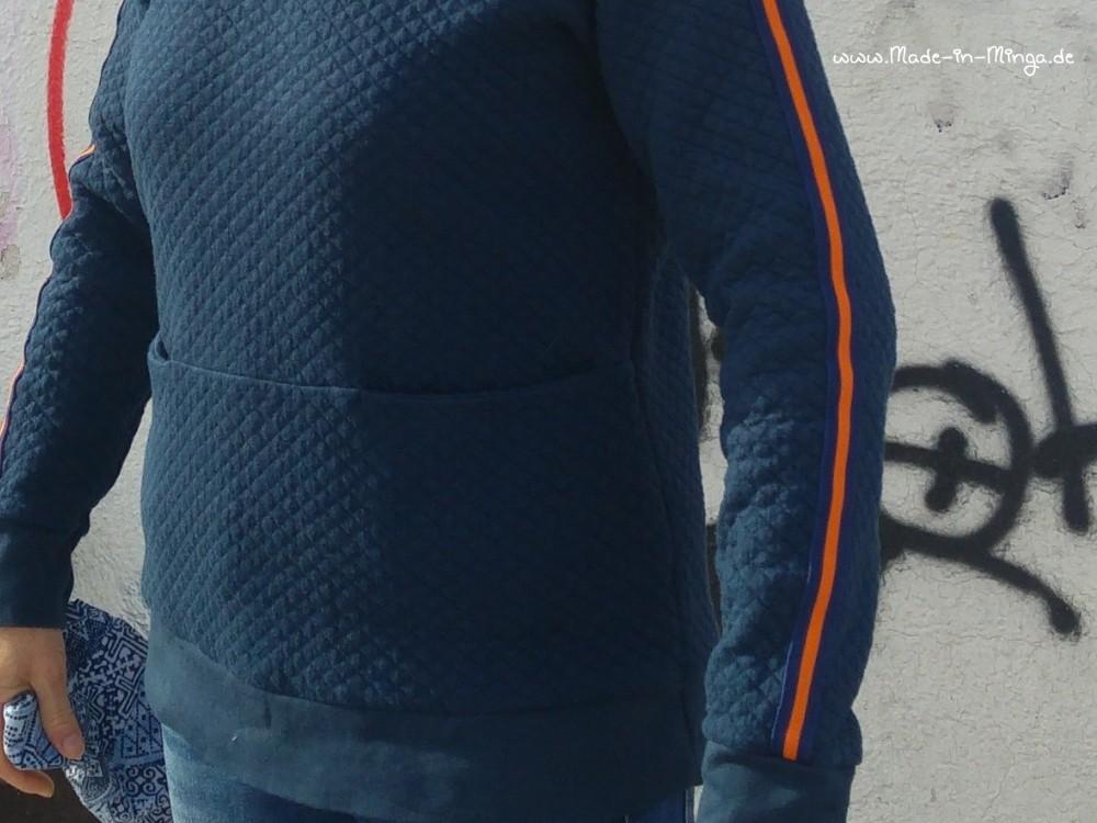 Bauchtasche am Pullover mit Quernaht, trägt etwas auf
