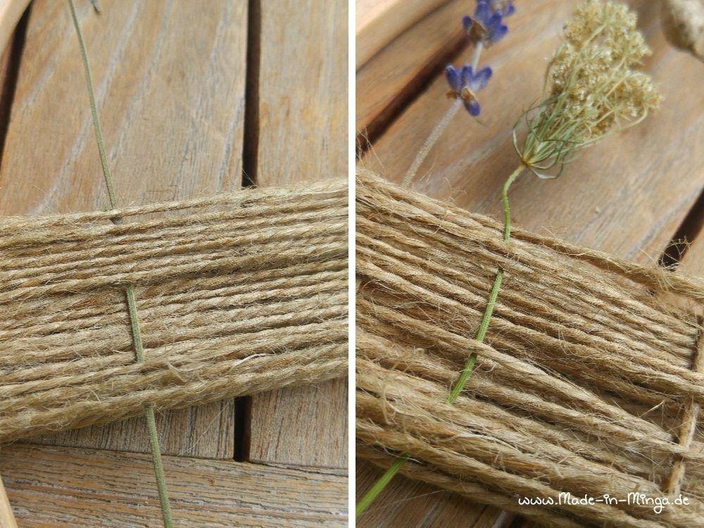 die Stiele der Trockenblumen in den Kranz weben